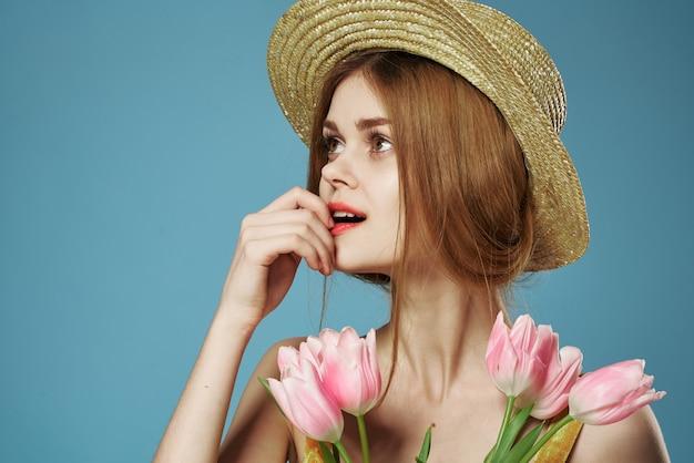 花の贈り物の花束と帽子のエレガントな女性はクローズアップを祝う