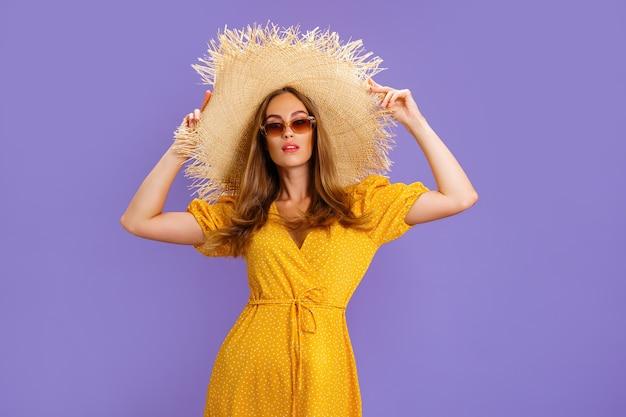 연한 노란색 여름 드레스 선글라스와 밀짚 모자를 쓴 우아한 여성이 보라색 벨벳 스튜디오에서 포즈를 취하고 있습니다...