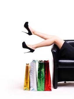 쇼핑 가방 흰색 배경에 고립 된 소파에 누워 검은 드레스에 우아한 여자.