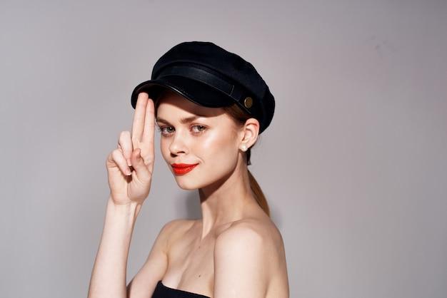 頭の孤立した背景に黒のイブニングドレスファッション化粧品帽子のエレガントな女性。