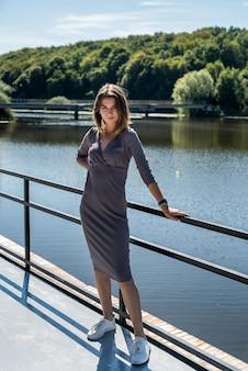 青い湖の近くに立っているファッションドレスのエレガントな女性