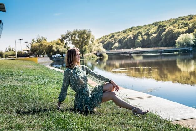 ファッションドレスのエレガントな女性が湖の近くに立っています