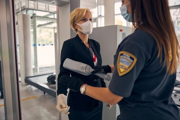 공항 터미널에서 금속 탐지기 스캐너를 통과하는 의료 얼굴 마스크에 우아한 여자