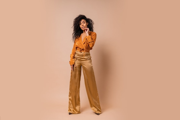 オレンジ色のブラウスとベージュの壁にポーズをとる金色のシルクのズボンのエレガントな女性。ハイヒール。驚くべきウェーブのかかった髪。完全な長さ。