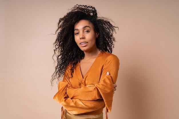 ベージュの壁にポーズをとる完璧な肌を持つオレンジ色のブラウスのエレガントな女性。ハイヒール。驚くべきウェーブのかかった髪。