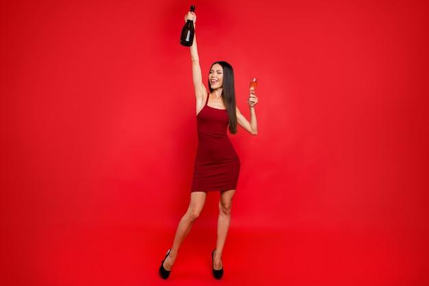Элегантная женщина в красном платье позирует у красной стены
