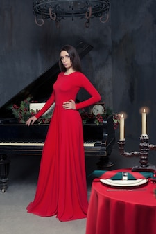 Элегантная женщина в красном платье, стоящая за ретро-роялем в ресторане с богатым винтажным интерьером.