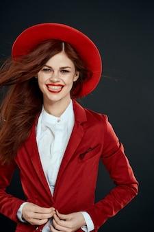 赤い帽子のブレザーの魅力的なライフスタイルのエレガントな女性