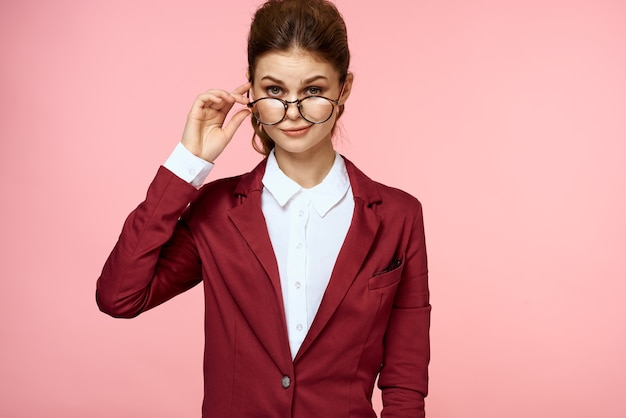 Элегантная женщина в красной куртке очки офис-менеджер розовый фон. фото высокого качества