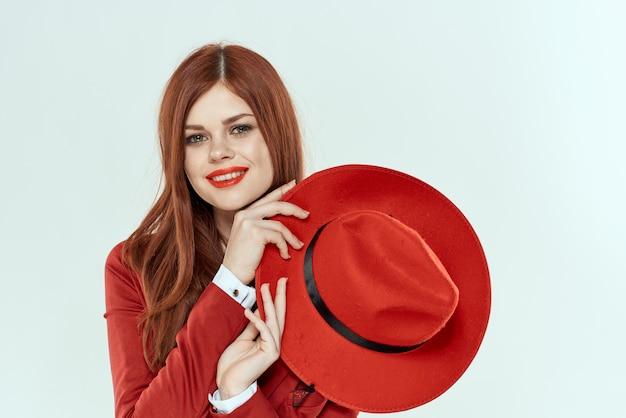 Элегантная женщина в красной куртке, держа шляпу