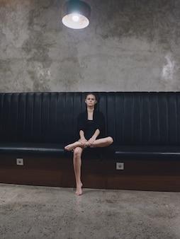 空港のデザインのインテリアを待っている屋内のソファに座って裸足でスーツを着たエレガントな女性
