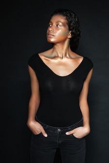 目をそらしているスタジオでtシャツを着たエレガントな女性。ポケットに手を入れます。孤立した黒