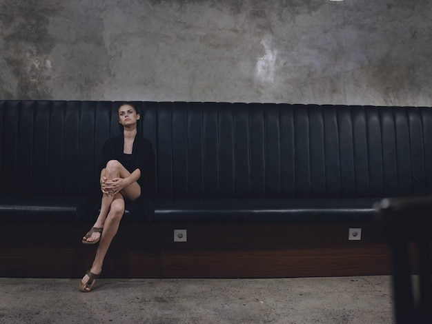 完全な長さで足を組んで屋内のソファに座っている流行の服を着たエレガントな女性