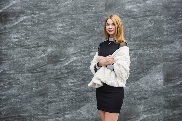 Elegant woman in little black dress and with fur scarf posing outside. fashion concept