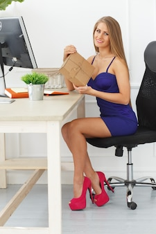 Elegant woman opens a package