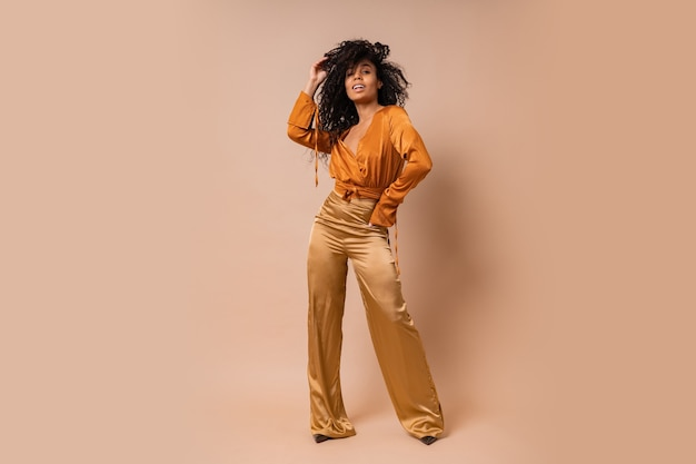 Elegant woman in orange blouse  and golden silk pants   posing  over beige wall. hight heels. amazing wavy hairs. full lenght.