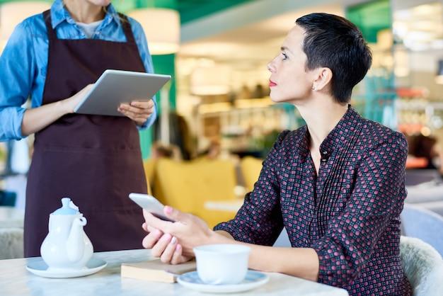 Элегантная женщина заказывает еду в кафе