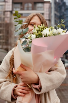 Elegant woman outdoors smelling bouquet of flowers
