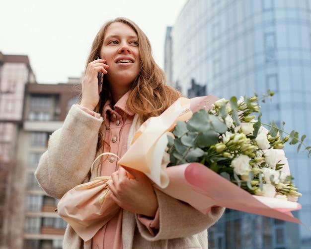 Donna elegante all'aperto parlando sullo smartphone e tenendo il mazzo di fiori