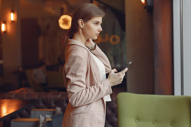 Elegant woman in a pink jacket spend time in a cafe