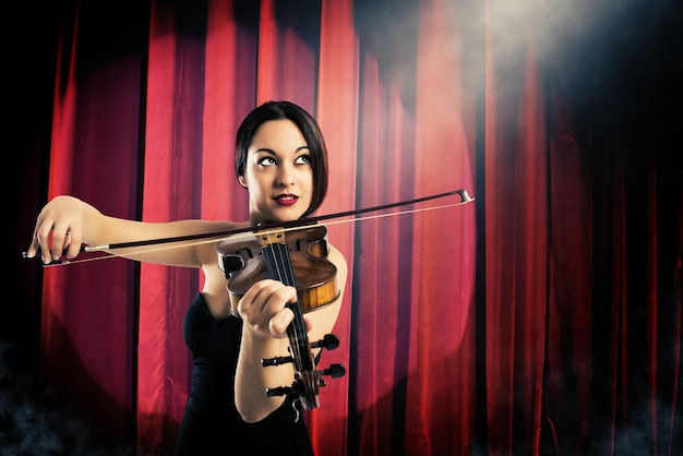 Элегантная женщина играет на скрипке на фоне красных занавесок в театре