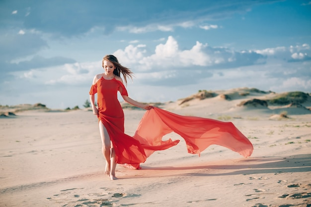 Elegant woman posing on the beach with red dress