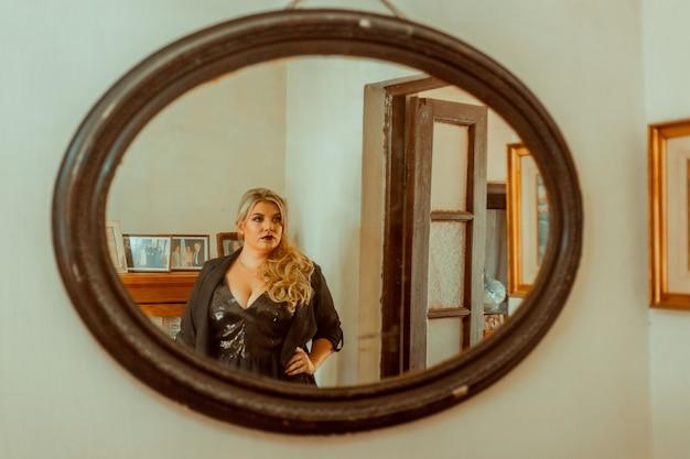거울 앞에서 포즈를 취하는 우아한 여자