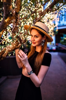 Elegant woman posing at luxury hotel terrace near tree with holiday lights