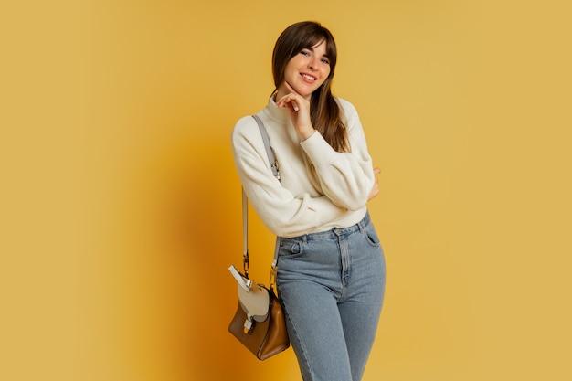 Donna elegante in posa in studio su giallo. indossa un maglione di lana bianca e jeans.