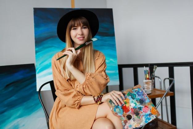 エレガントな女性が新しい彼女のアート作品でポーズします。