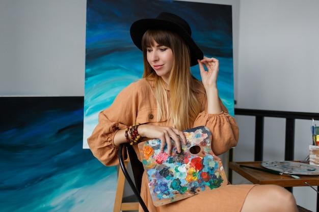 Donna elegante che posa con la nuova sua opera d'arte.