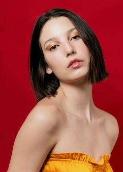 Elegant woman posing in yellow top