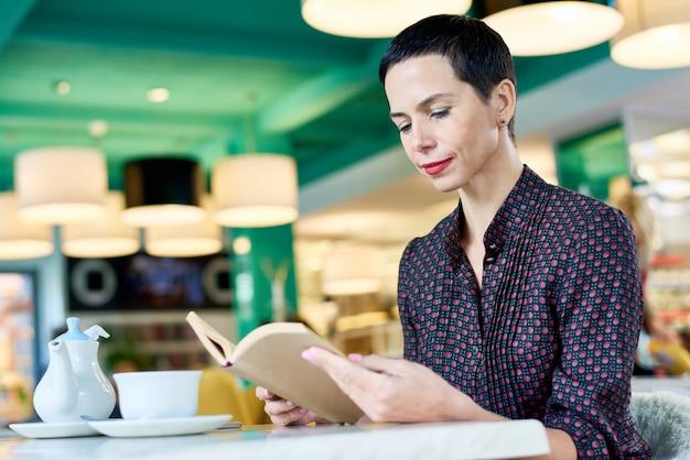 Элегантная женщина читает книгу в кафе