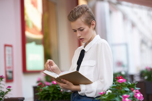 Elegant woman in shirt with tie and book in hand cafe street trees flowers