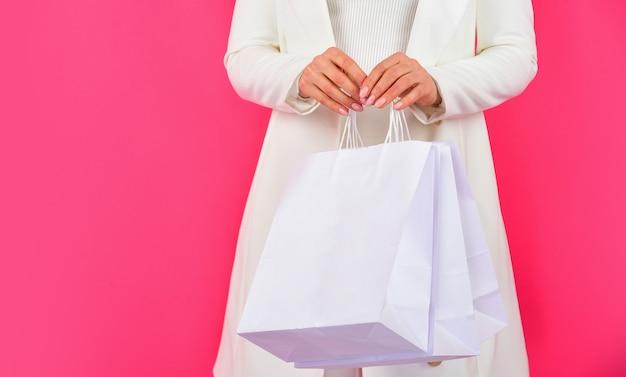 エレガントな女性の買い物中毒の女の子の買い物客は紙袋のパッケージを保持しますプレゼントオンラインギフトショップを購入します