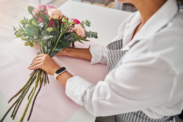 Элегантная женщина сидит за столом с букетом цветов
