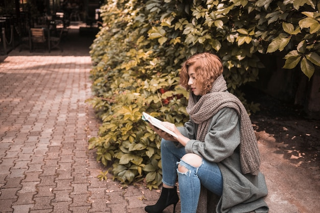 Elegant woman sitting on board and attentively reading book near plant