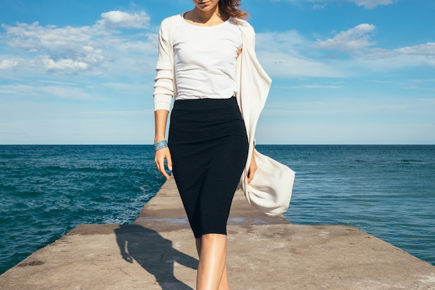 Elegant woman in a skirt and cardigan walks, sea on a sunny day