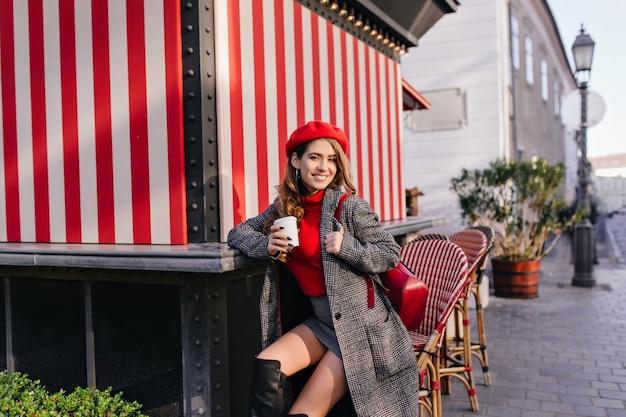 Donna elegante in gonna e cappotto che beve caffè per strada con un sorriso dolce