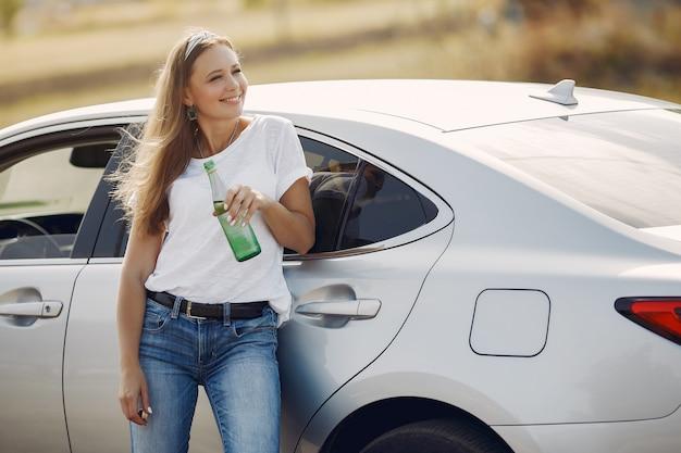 車で立っているエレガントな女性