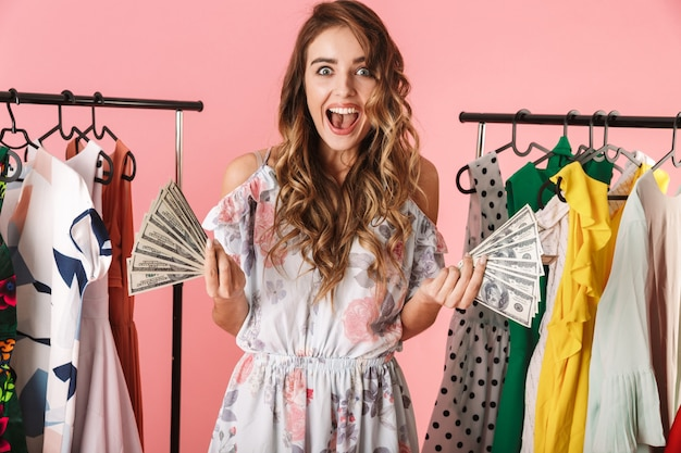 Elegant woman standing near wardrobe while holding colorful shopping bags and credit card isolated on pink