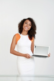 Elegant woman standing at the white wall and showing the screen of her laptop