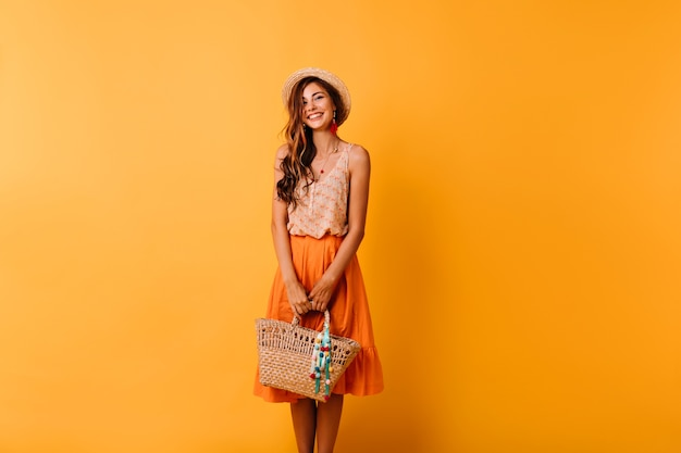 Elegant woman in summer outfit preparing for vacation. romantic ginger girl in straw hat posing on orange with bag.