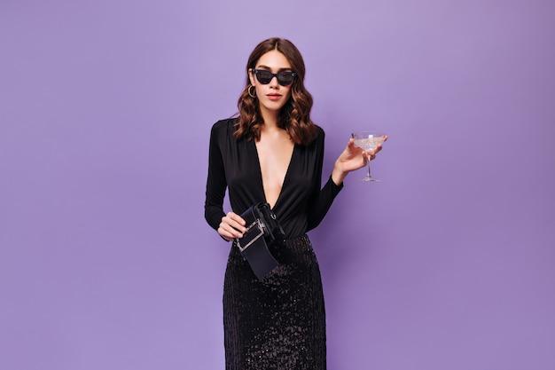La donna elegante in occhiali da sole e vestito nero tiene il bicchiere da martini