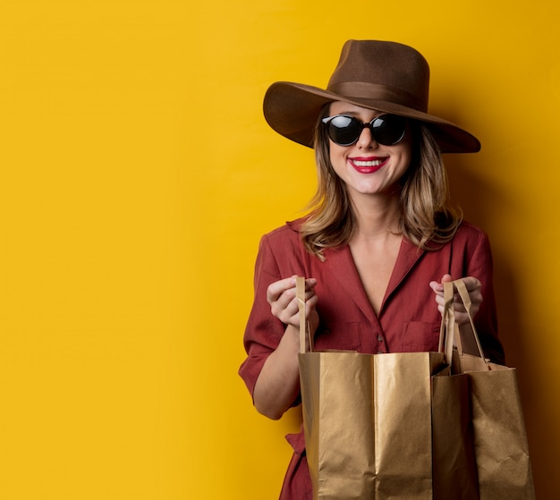 Elegant woman in sunglasses and with shopping bags