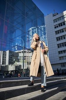 路上で携帯電話で話しているエレガントな女性