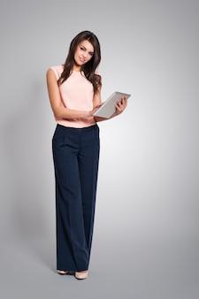 Donna elegante utilizzando la tavoletta digitale contemporanea