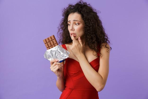 Элегантная женщина в красном платье держит плитку шоколада, стоя изолированно над фиолетовой стеной