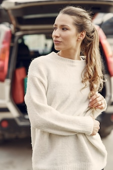 Elegant woman in a white sweater in a spring city