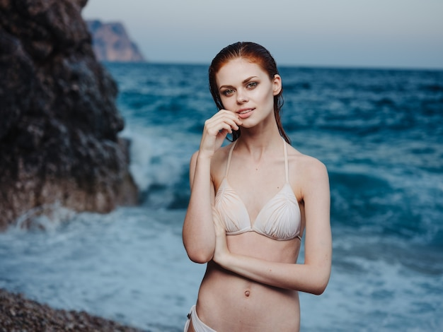 Elegant woman in white swimsuit bare shoulders transparent water ocean beach nature. high quality photo